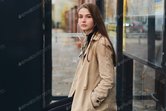 Attractive casual girl in earphones intently looking in camera waiting public transport on bus stop