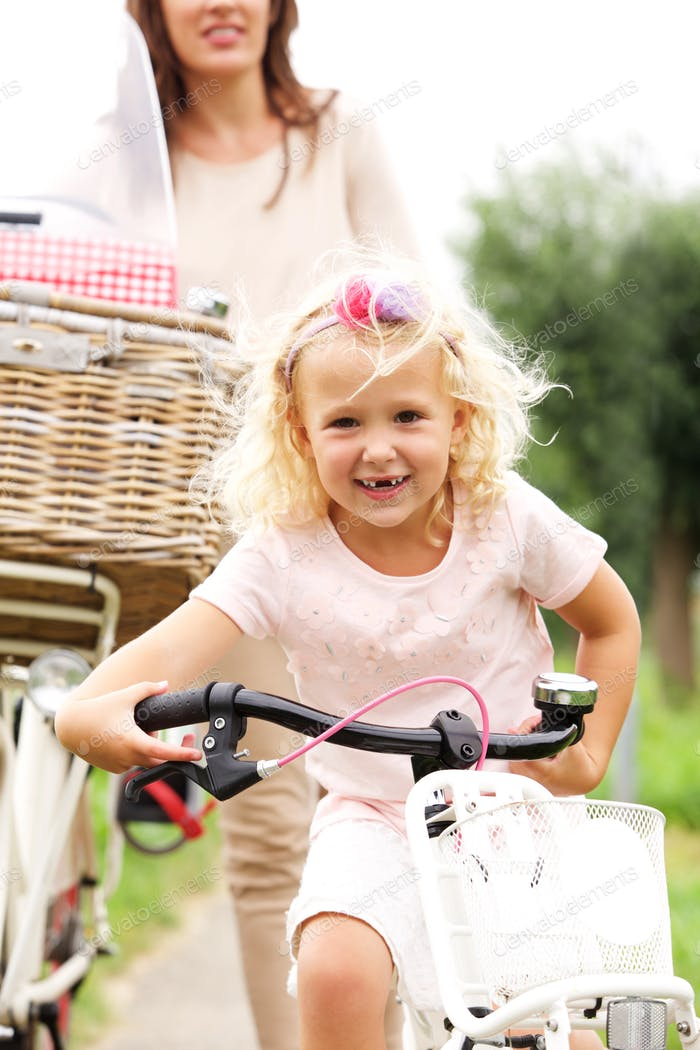 Cute little girl cycling in park with mother in background