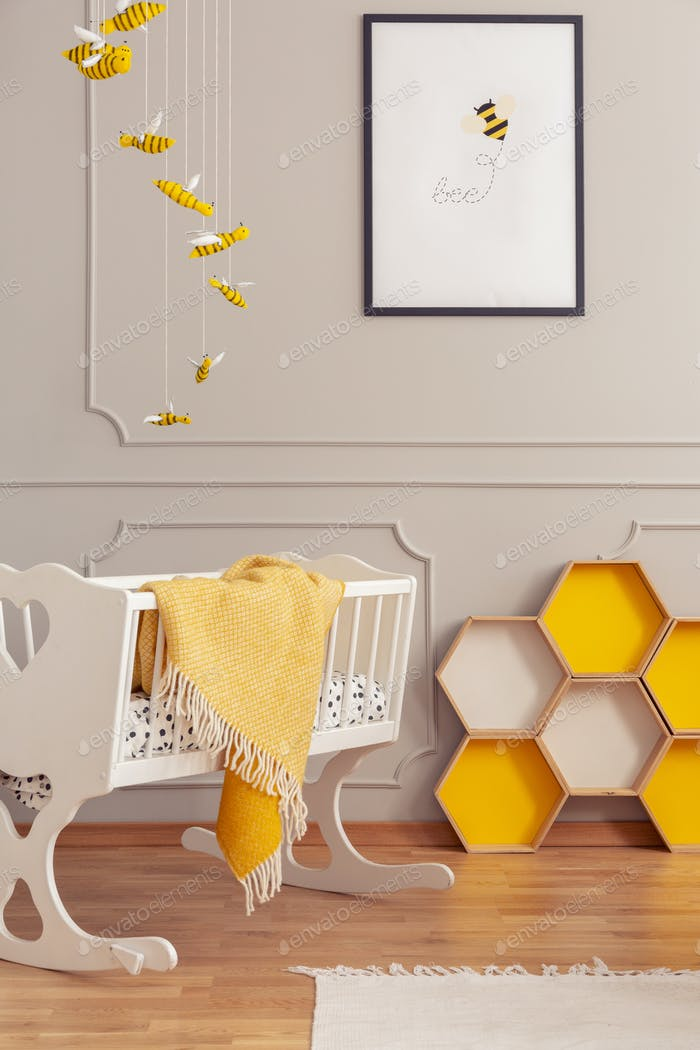 Cot with a blanket and yellow honeycombs in a kid room interior.