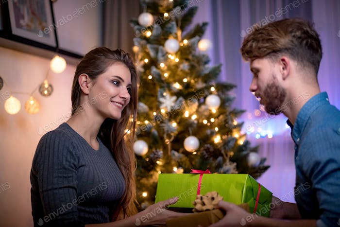 Happy couple are giving themselves Christmas gifts next to Xmas tree at holiday evening