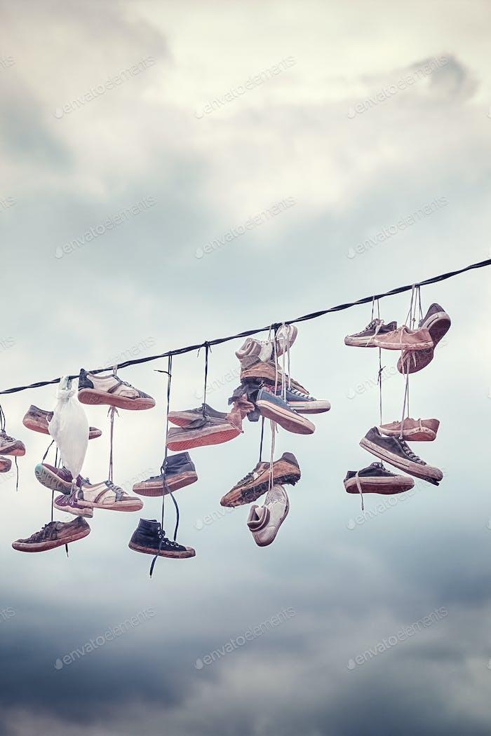 Alte Schuhe hängen an Draht.