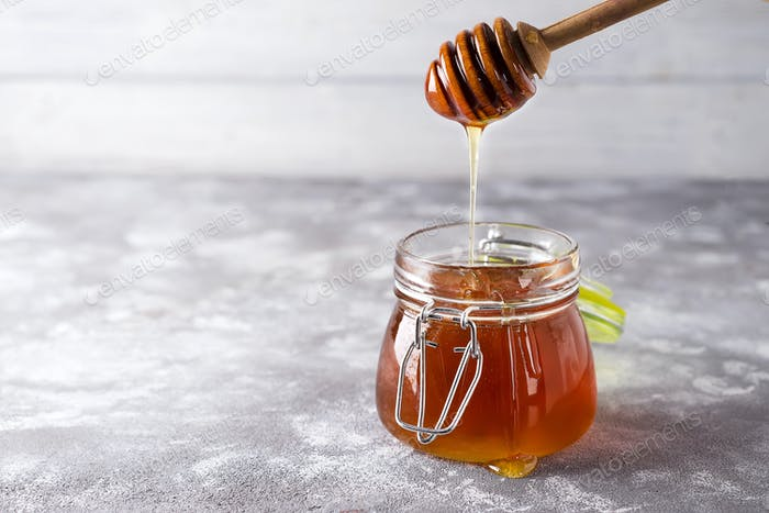 Spoon of honey with jar on a light background