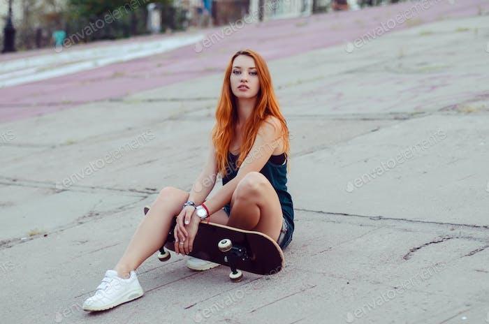 Redhead skater girl posing in skate park.