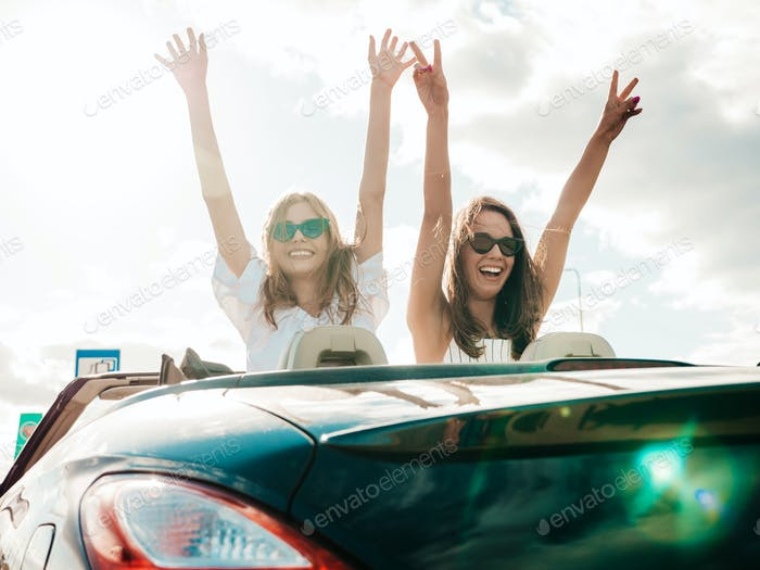 Portrait of two young funny women driving cabriolet