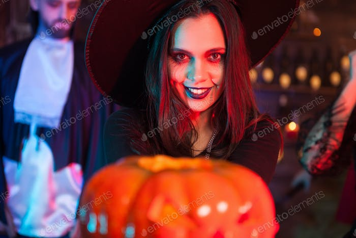 Sexy witch holding a magic pumpking with a scary expression for halloween party