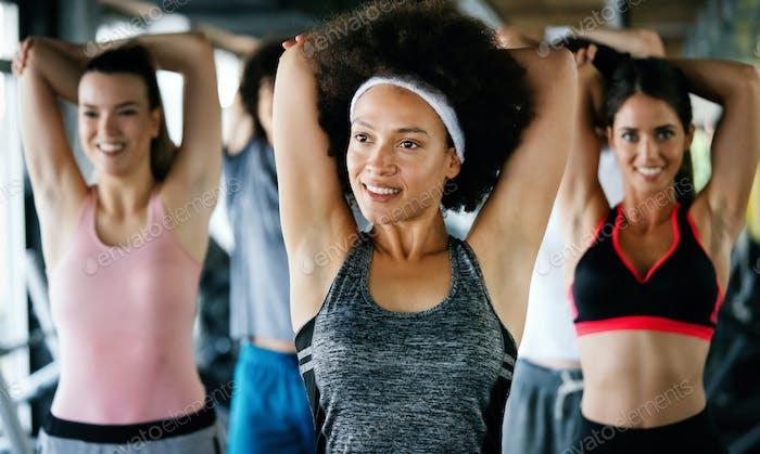 Diversity Gruppe von Menschen Training in einem Fitnessstudio. Trainer und sportliche Personen, die trainieren