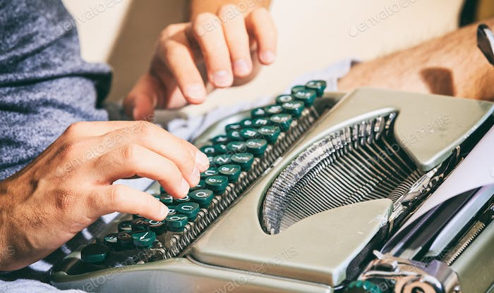 Man hands typing on a vintage typewriter.