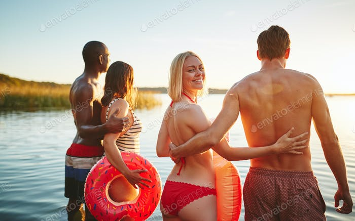 Smiling woman and friends watching the sunset at a lake