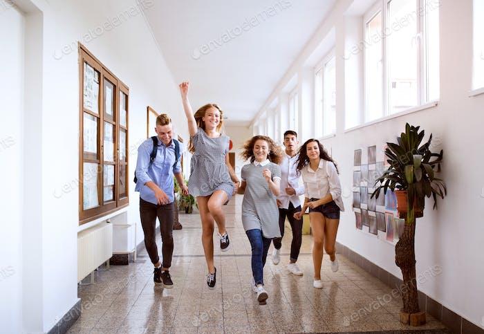 Teenage students in high school hall jumping high.