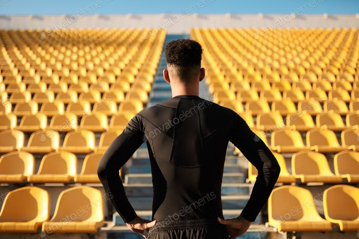 Back view of young African American sportsman among empty stadium seats