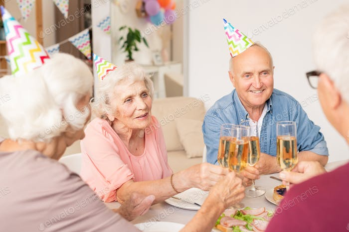 Group of happy senior friends clinking with flutes of champagne