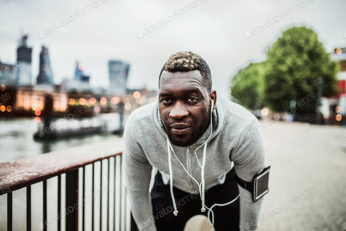 Black man runner with smart watch and smartphone on the bridge in a city, resting.