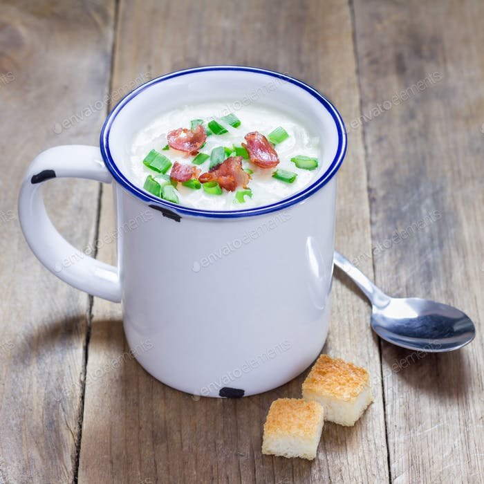 Creamy potato soup garnished with bacon and green onion, served in mug, square format