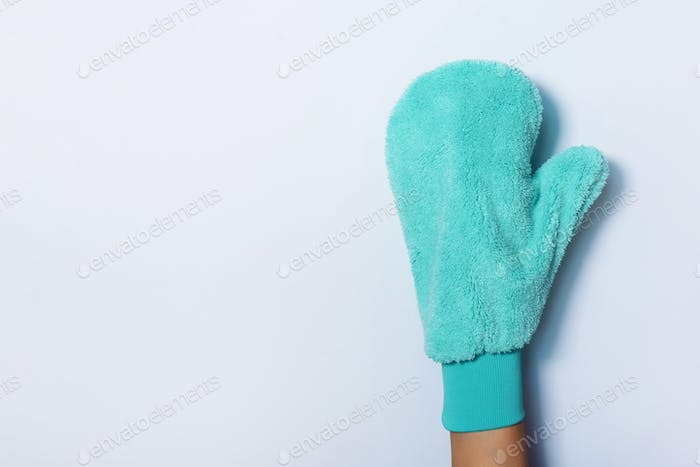 Hand in glove holding microfiber cleaning cloth, cleaning mitten on white background. Copy space