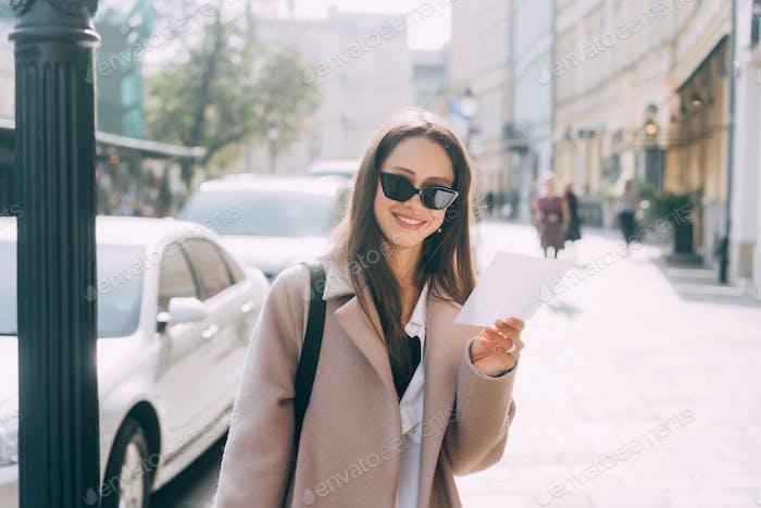 Young stylish woman posing at the street and looking at camera