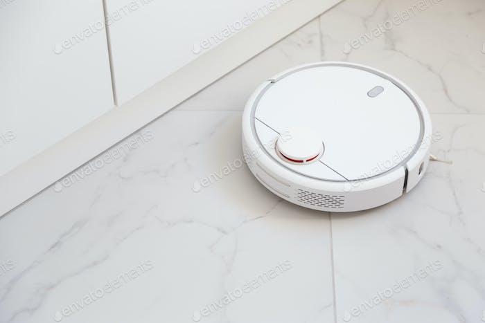Robot vacuum cleaner vacuuming tiles in room