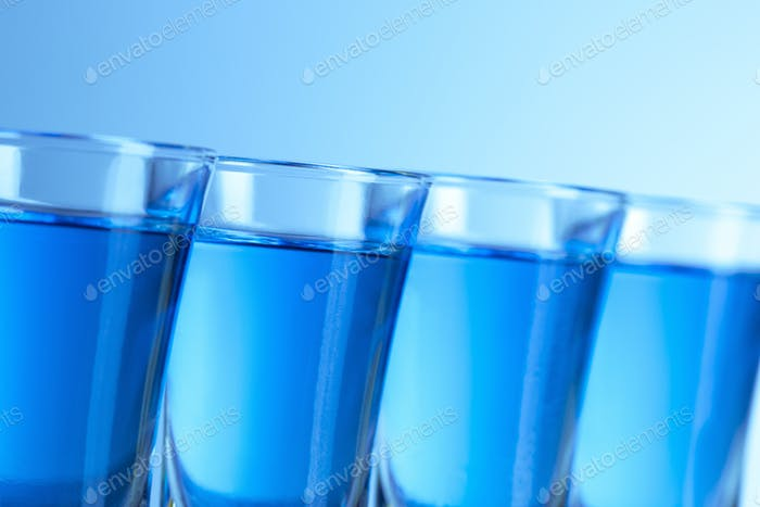 Vodka glass with ice on blue background