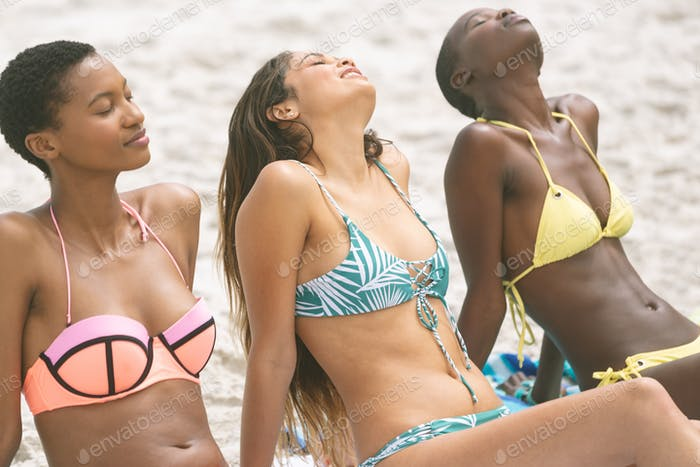 Front view of multi ethnic women with bikini relaxing sitting on sable on beach