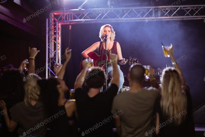 Weibliche Performerin singt während der Musikveranstaltung