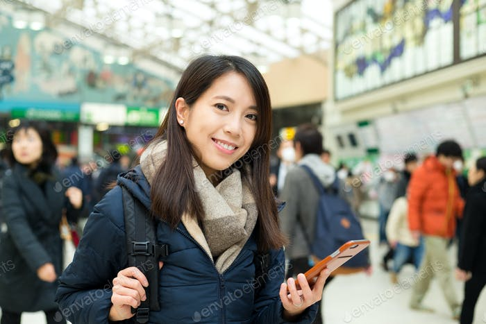Женщина использование мобильного телефона в железнодорожном вокзале