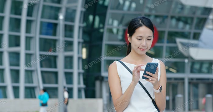 Woman search on cellphone in city