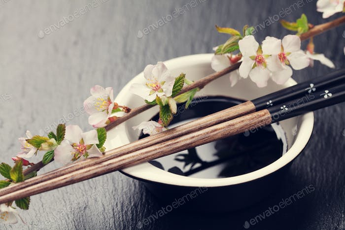 Japanese sushi chopsticks, soy sauce bowl and sakura blossom