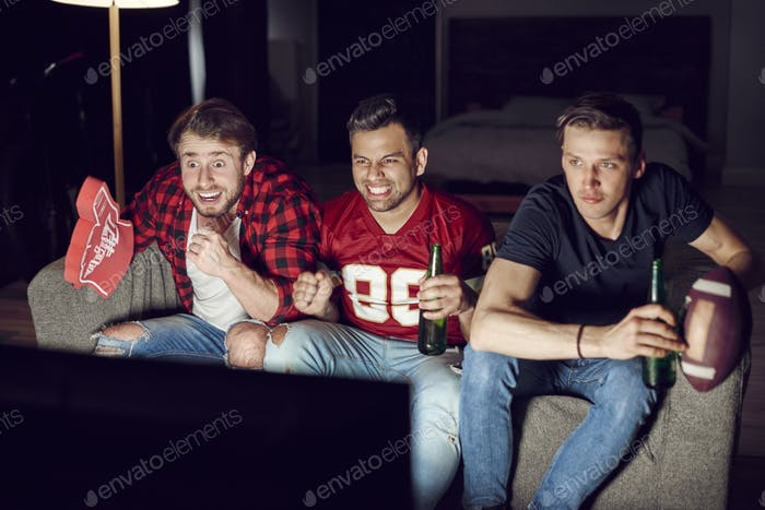 Excited football fans watching american football in the evening