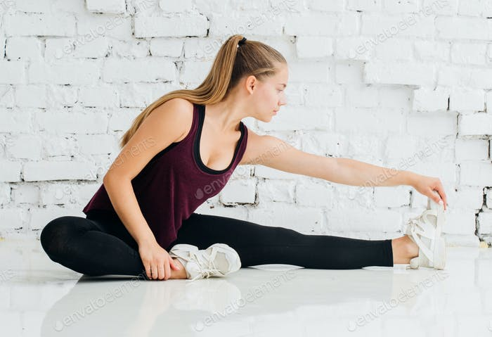 Woman stretching sport at home over brick wall