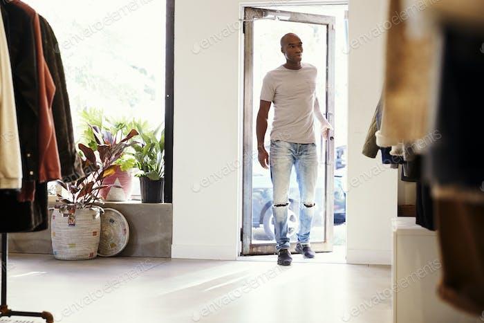 joven negro Hombre caminando en un tienda de ropa y cerrando Puerta