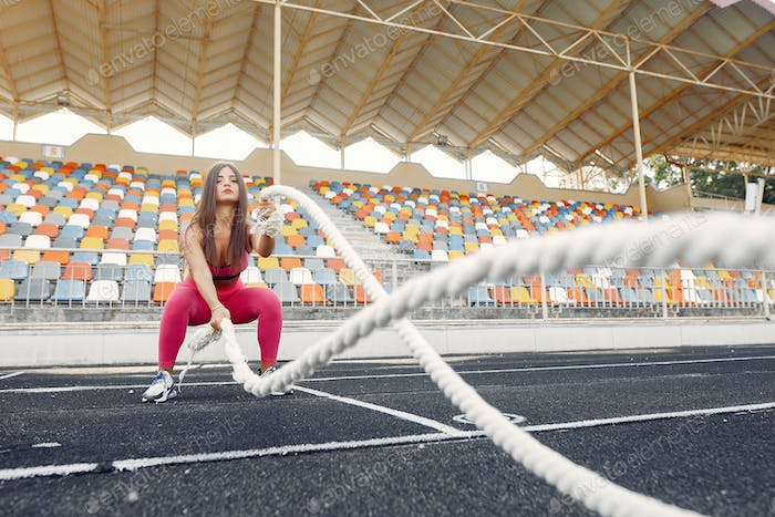 Sports girl in a pink uniform training with rope at the stadium