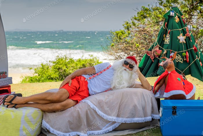 Relaxed Santa Claus lying on the beach