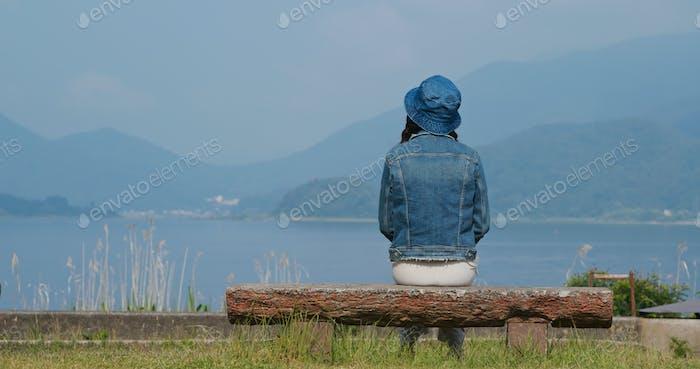 Mujer mira el lago y sentarse en el banco
