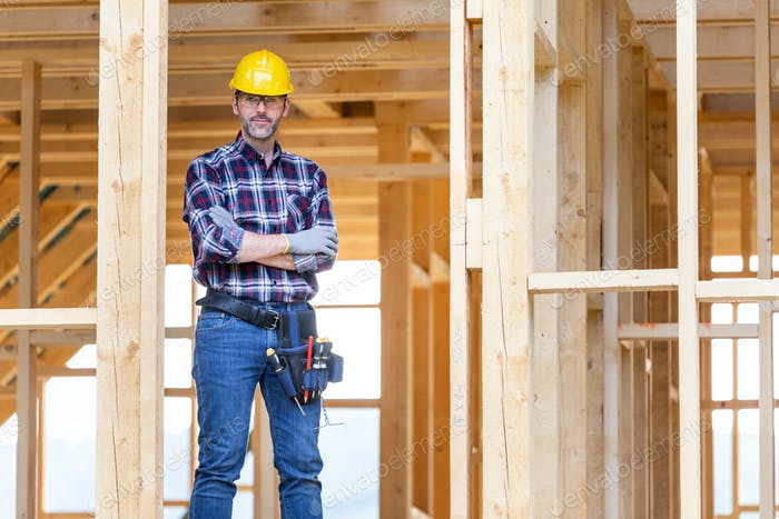 Builder worker on construction site of frame house