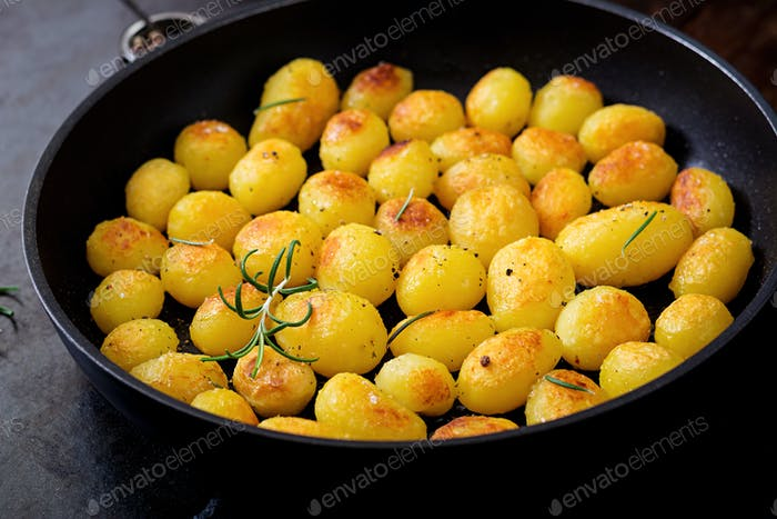 Baked potatoes with rosemary and pepper in a frying pan on black background