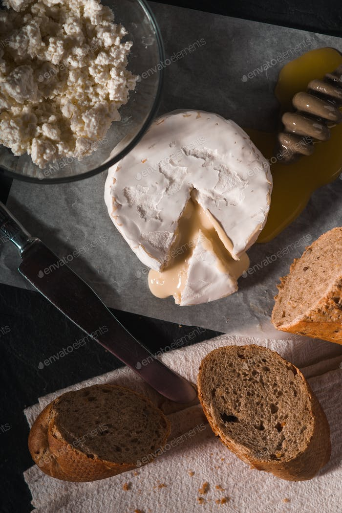 Brie cheese with honey and bread on the background