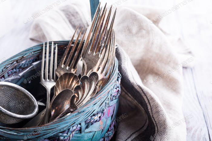 Vintage cutlery in old blue wicker basket