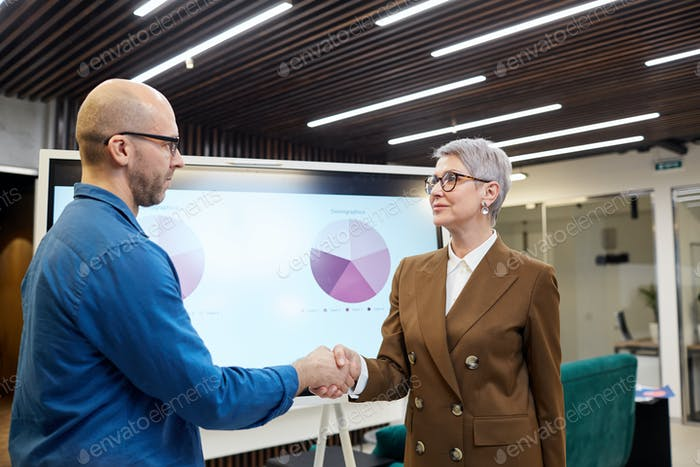 Mature Female Manager Shaking Hands with Client