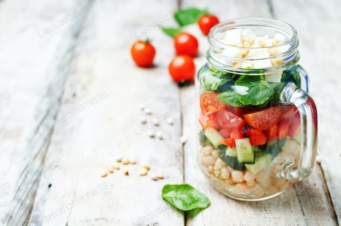 White beans cucumber tomato red pepper feta spinach salad in a j