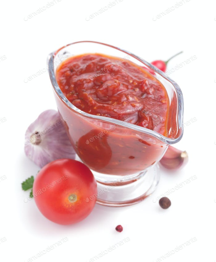 tomato sauce in gravy boat on white