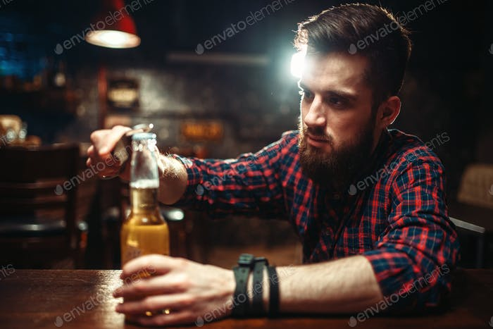 Man sitting at the bar counter and opens bottle