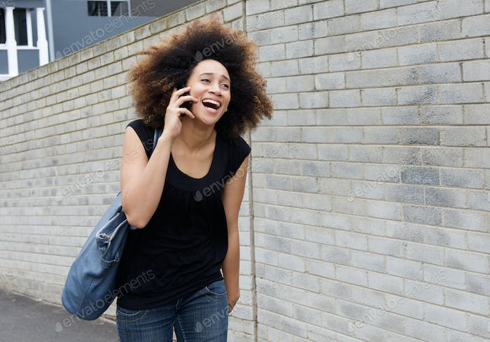 Young woman walking and laughing on mobile phone