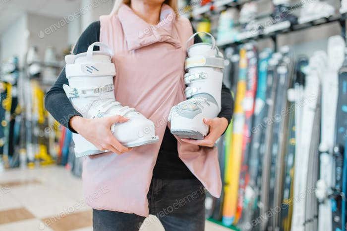 Woman shows ski or snowboarding boots, sports shop