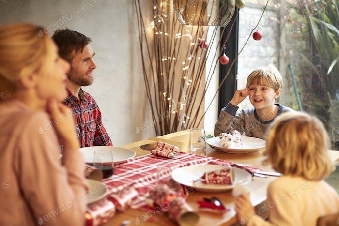 Uma família de quatro pessoas em uma refeição de Natal, puxando bolachas