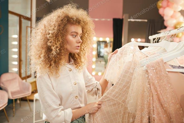 Young Woman Choosing Beautiful Dresses in Boutique