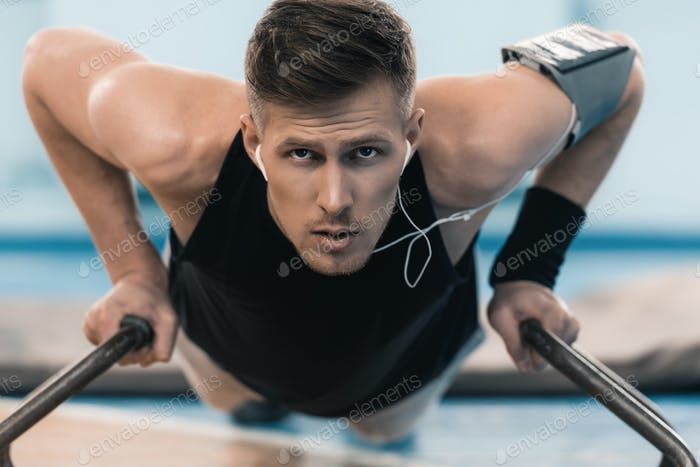 Young concentrated sportsman exercising on parallel bars and looking at camera