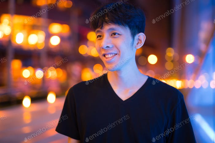 Happy Asian Man Thinking Outdoors At Night