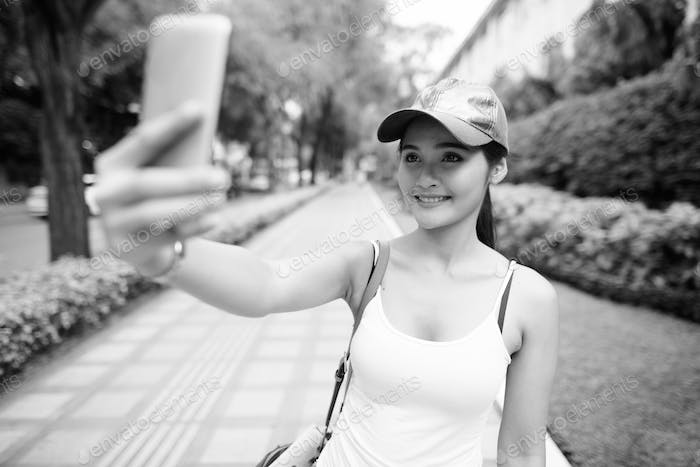 Happy young beautiful Asian tourist woman taking selfie in the city streets