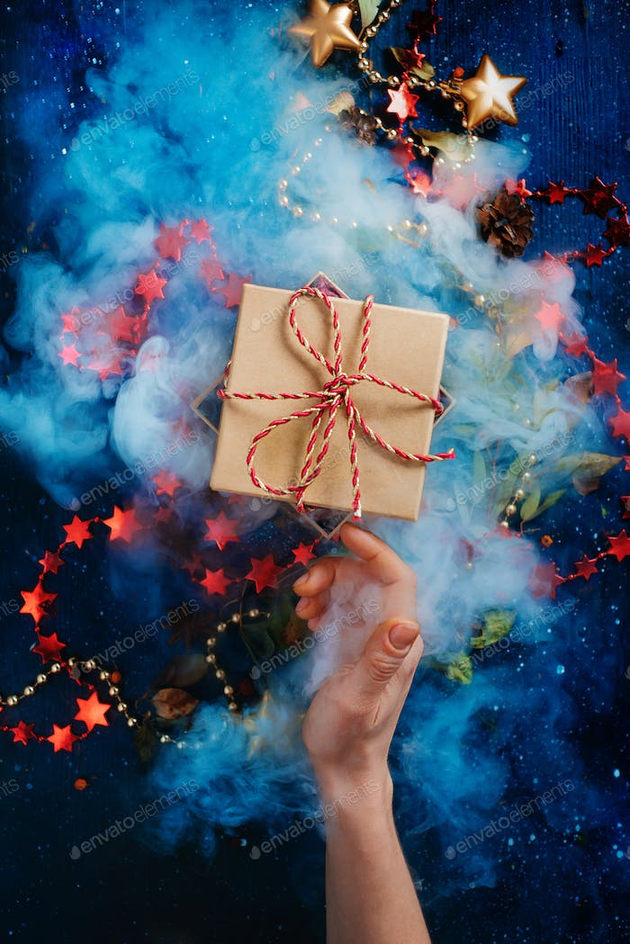 Christmas surprise concept, a gift box with dence steam and a reaching hand on a dark background