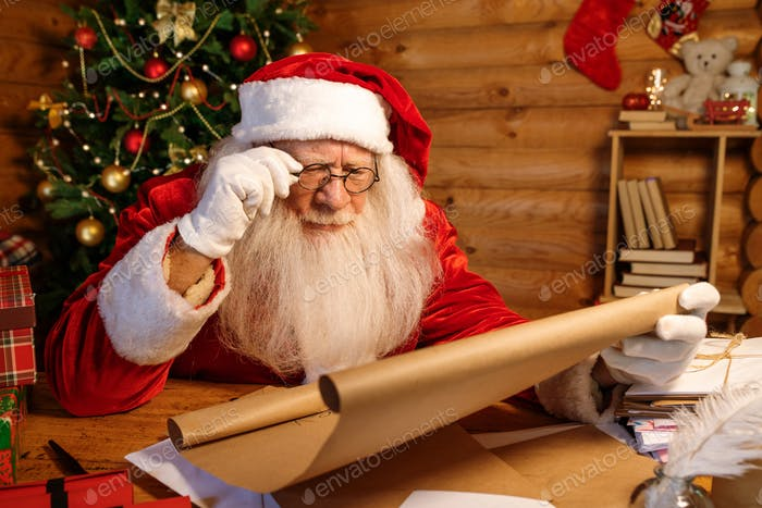 Santa in eyeglasses reading attentively big letter of Christmas wishes