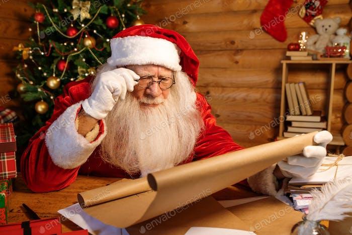 Weihnachtsmann in Brille lesen aufmerksam großen Brief der Weihnachtswünsche